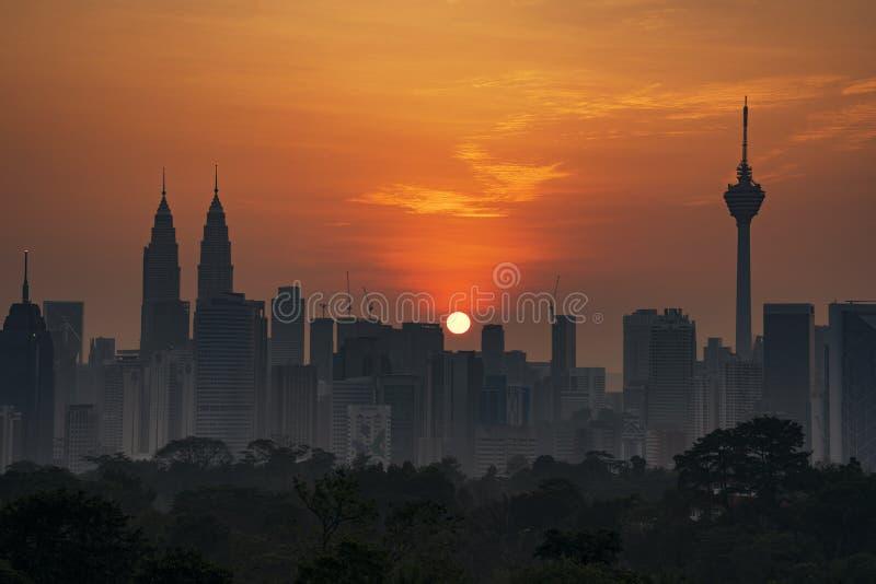 Kuala Lumpur, MALÁSIA - cerca do fevereiro de 2018: Skyline da cidade de Kuala Lumpur durante o nascer do sol obscuro imagem de stock royalty free