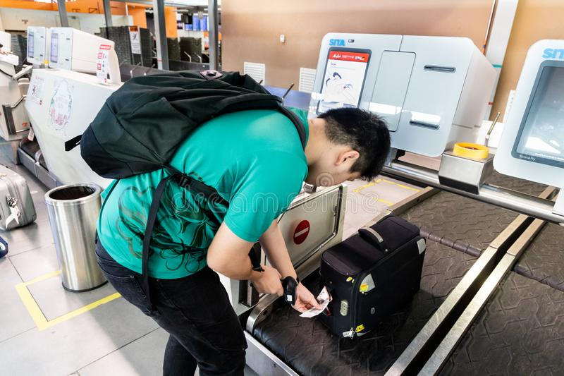 KUALA LUMPUR, MALÁSIA 7 DE JUNHO DE 2019: Pessoa que executa o auto - verificação - dentro da bagagem na facilidade do registro d imagem de stock royalty free