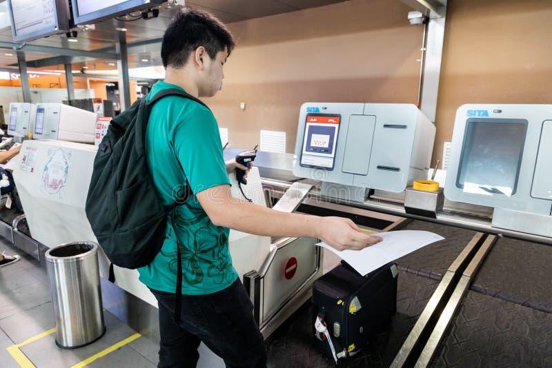 KUALA LUMPUR, MALÁSIA 7 DE JUNHO DE 2019: Pessoa que executa o auto - verificação - dentro da bagagem na facilidade do registro d fotografia de stock