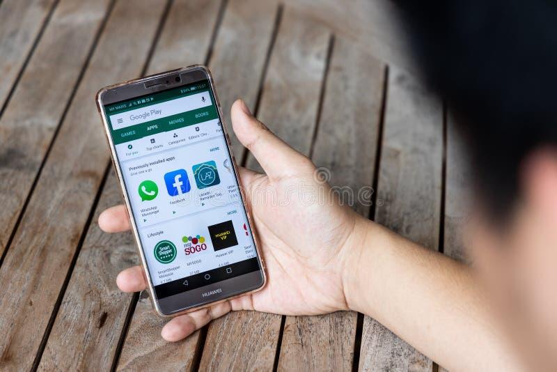 KUALA LUMPUR, MALÁSIA, O 21 DE MAIO DE 2019: Pessoa que guarda o telefone do companheiro de Huawei com Google Play Store U S as e foto de stock