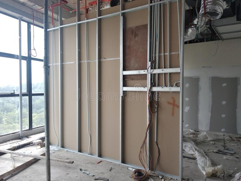 Drywall installation work in progress by construction workers at the construction site. royalty free stock photography