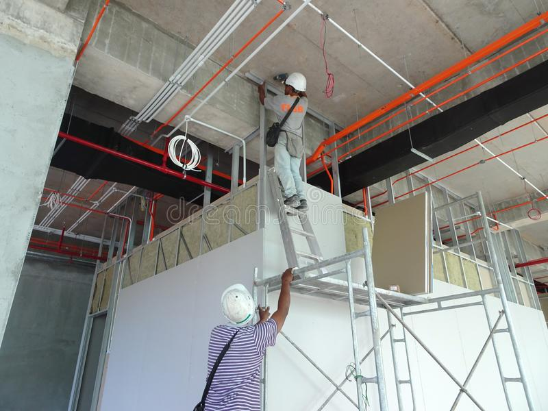 Drywall installation work in progress by construction workers at the construction site. stock image