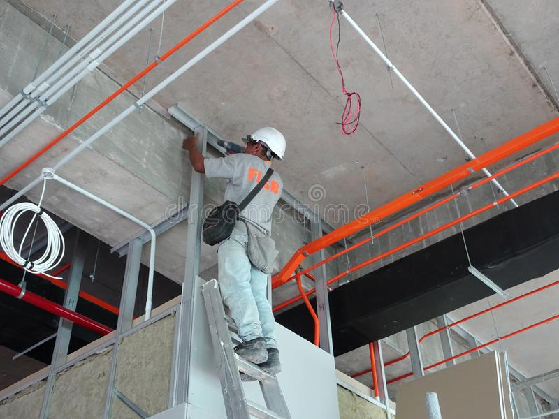 Drywall installation work in progress by construction workers at the construction site. stock photography