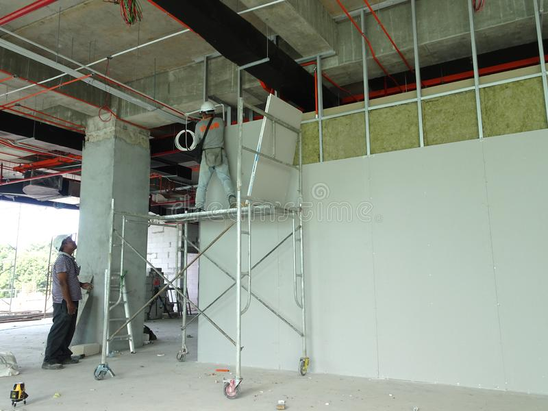 Drywall installation work in progress by construction workers at the construction site. royalty free stock image