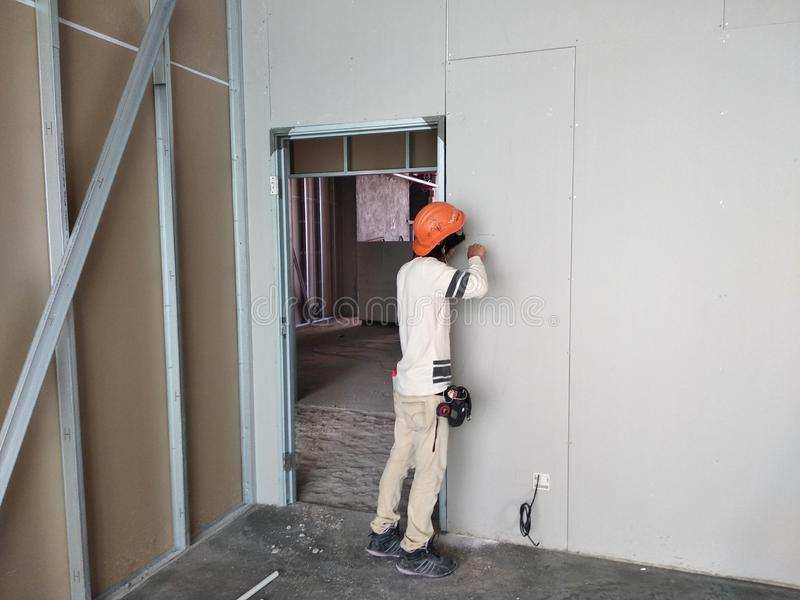 Drywall installation work in progress by construction workers at the construction site. royalty free stock photo