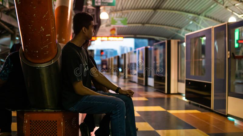 Unidentified boys waiting for the LRT train to stop at the Imbi station. Kuala Lumpur, Malaysia - April 5, 2019: Unidentified boys waiting for the LRT train to stock images