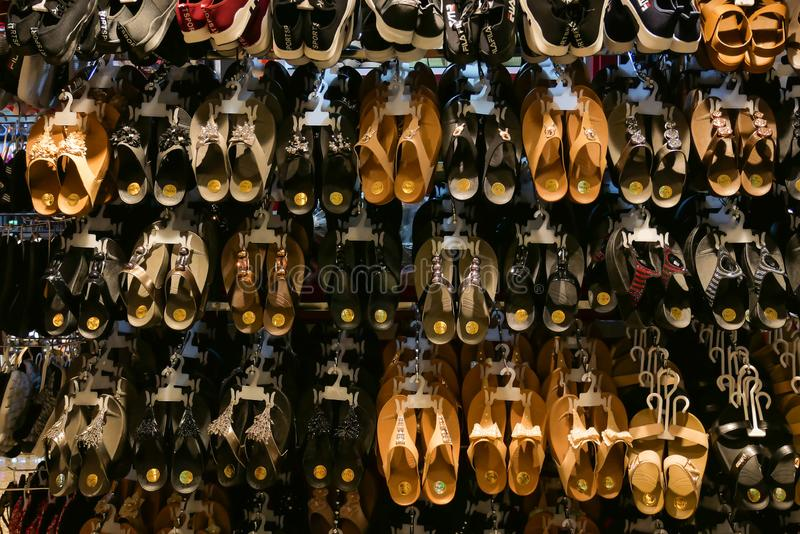 Various pair of slippers hang on the shelves and display at the store for selling stock photo