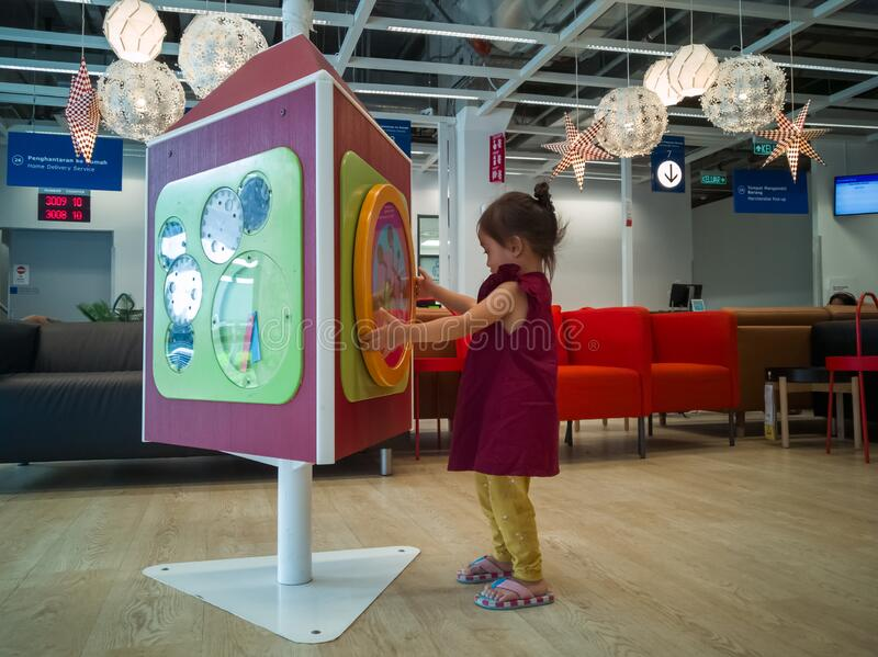 Toddler playing at the IKEA store in Cheras while waiting at the customer service area. Kuala Lumpur, Malaysia - Dec 30, 2019: Toddler playing at the IKEA store royalty free stock photos