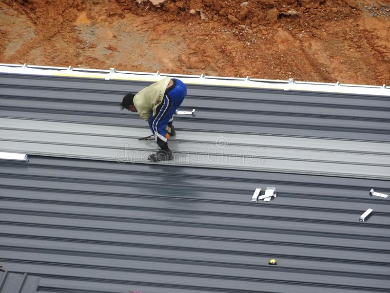 Installation of metal deck roof sheet by construction workers. royalty free stock image