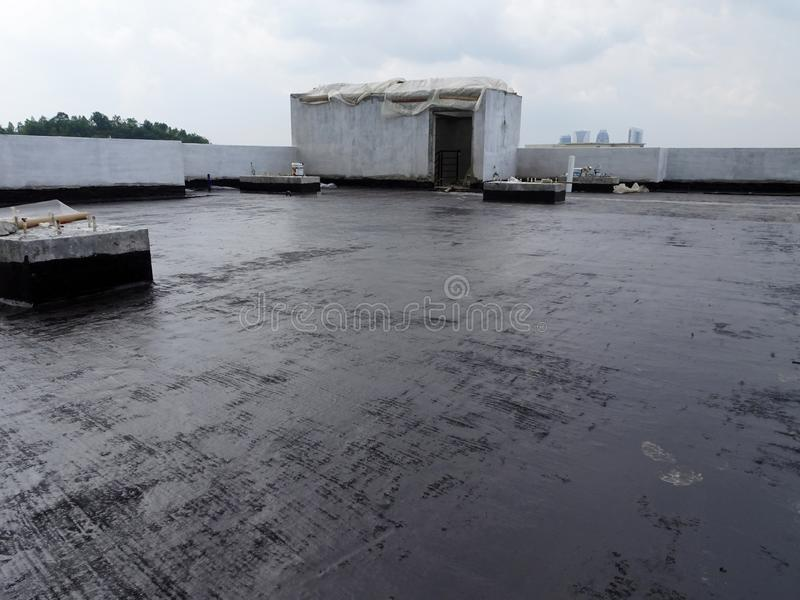 Waterproofing membrane applied by construction workers on top of the concrete slab. KUALA LUMPUR, MALAYSIA -JULY 25, 2018: Waterproofing membrane applied by stock photography