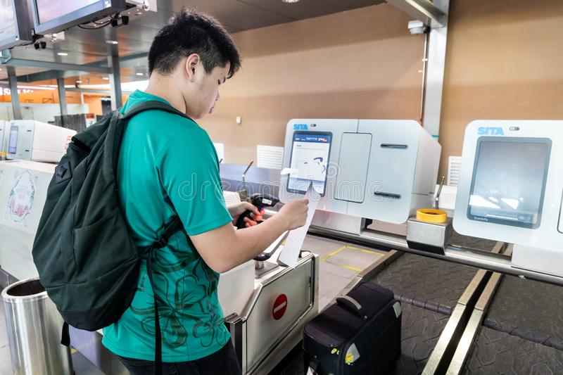 KUALA LUMPUR, MALAYSIA JUNE 7, 2019: Person performing self check-in of luggage at airport luggage check-in facility stock images