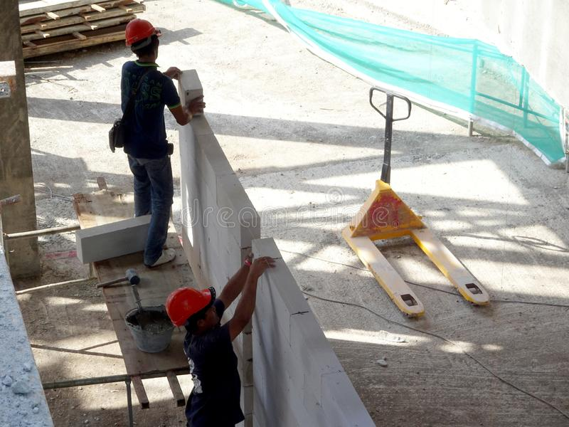Construction workers installing lightweight block bricks to become wall at the construction site. KUALA LUMPUR, MALAYSIA -MARCH 29, 2017: Construction workers royalty free stock photography