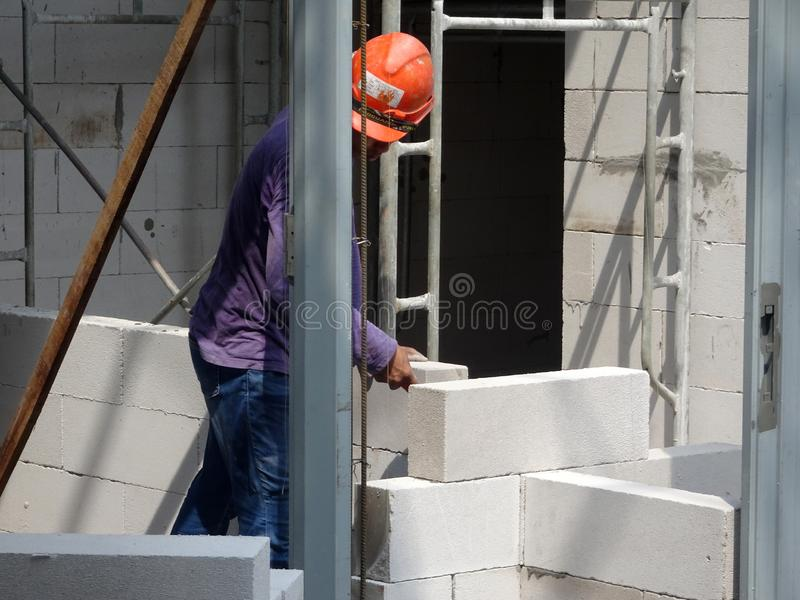 Construction workers installing lightweight block bricks to become wall at the construction site. KUALA LUMPUR, MALAYSIA -MARCH 29, 2017: Construction workers royalty free stock photo