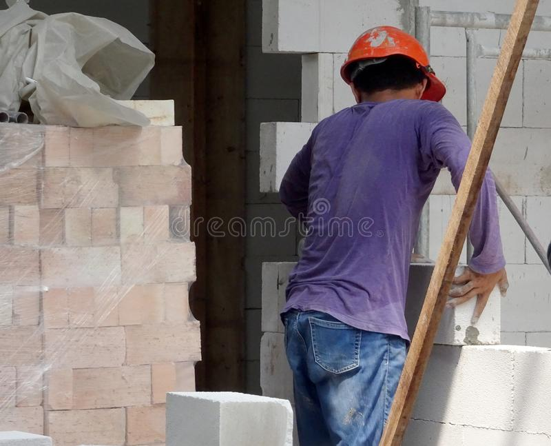 Construction workers installing lightweight block bricks to become wall at the construction site. KUALA LUMPUR, MALAYSIA -MARCH 29, 2017: Construction workers stock photos