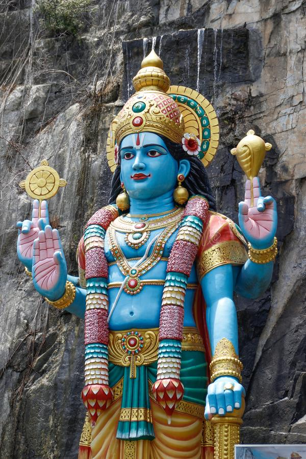 A sculpture of an Indian god at the entrance to the caves royalty free stock photo