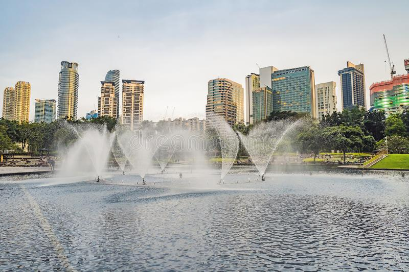 Kuala Lumpur, Malaysia, November 18, 2018: Fountain on the lake in the evening, near by Twin Towers with city on royalty free stock image