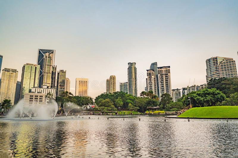 Kuala Lumpur, Malaysia, November 18, 2018: Fountain on the lake in the evening, near by Twin Towers with city on royalty free stock photos