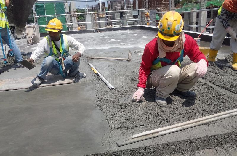 Construction workers leveling wet concrete has been poured. stock photography