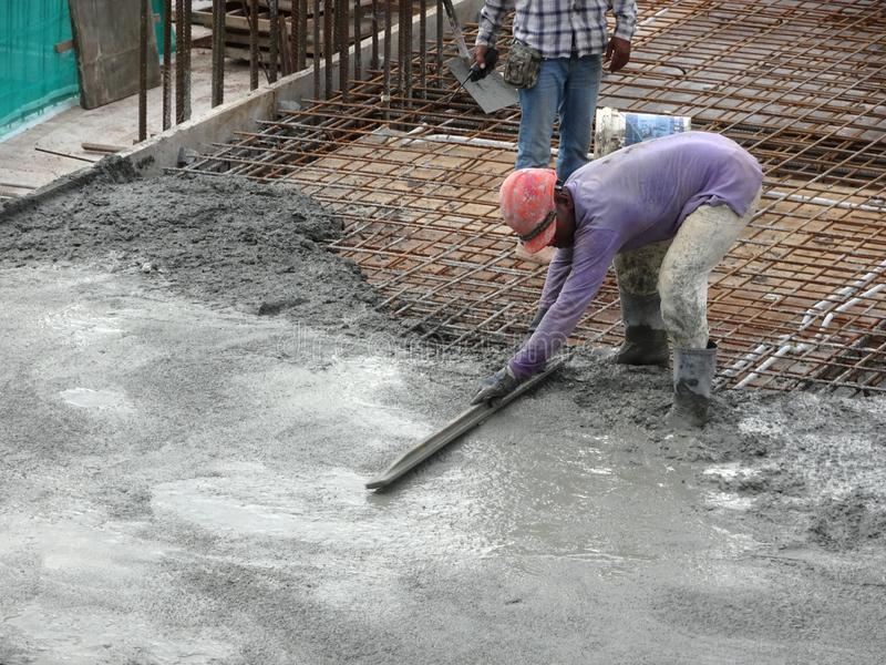 Construction workers leveling wet concrete has been poured. royalty free stock images