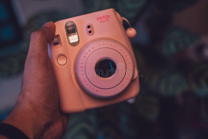 Kuala Lumpur, Maleisië - Augustus 31, 2018: Polaroid roze camera van Fujifilm van de handholding royalty-vrije stock afbeeldingen