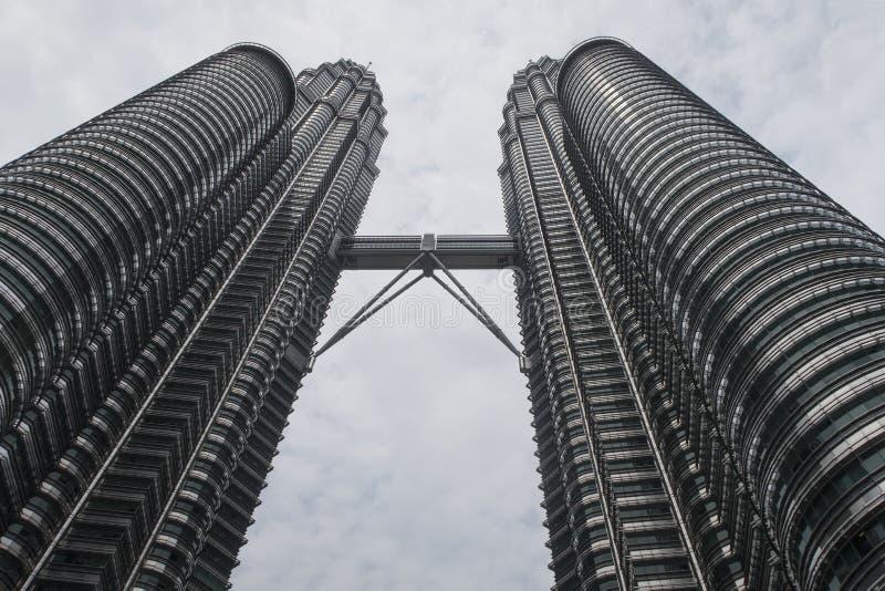 Kuala Lumpur, Maleisië - Juli 21, 2018; Petronas tweelingdietorens van grondniveau, een beroemd oriëntatiepunt en een winkelcompl stock afbeeldingen