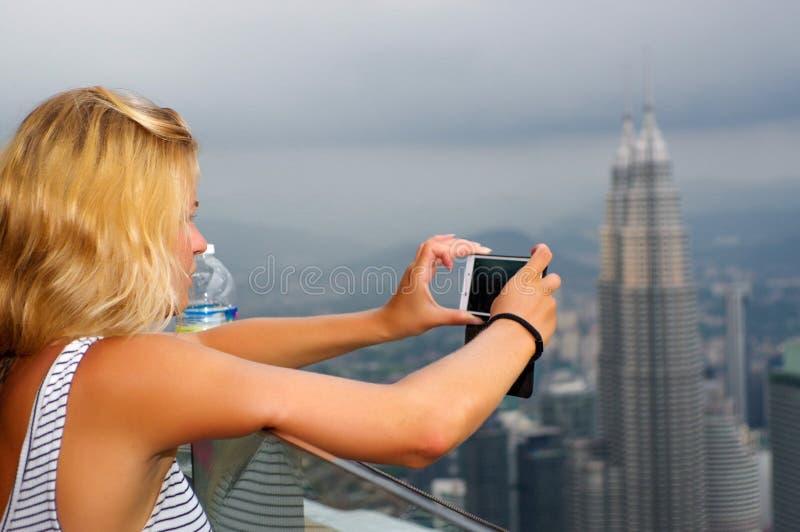 KUALA LUMPUR MALEZJA, Styczeń, - 17, 2016: Podróż i technologia Młoda kobieta bierze fotografię z smartphone od CC$KL wierza przy zdjęcie royalty free