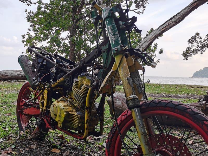 Kuantan, Malezja - 14 grudnia 2019:Widok starego, zardzewiałego motocykla w pobliżu plaży fotografia royalty free