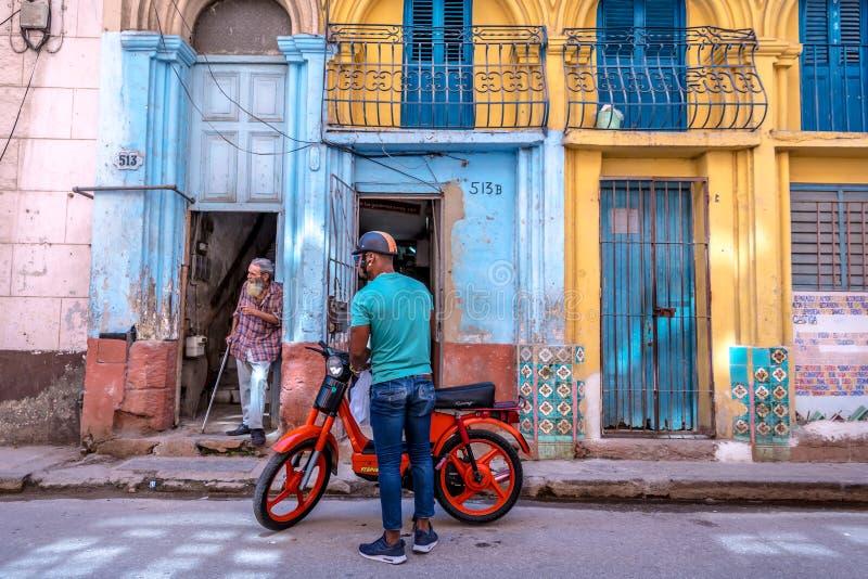 Kuba havannacigarr - fördärva 9th 2018 - lokalt folk av havannacigarren som framme parkerar en gammal, mycket enkel motorcykel av arkivfoton
