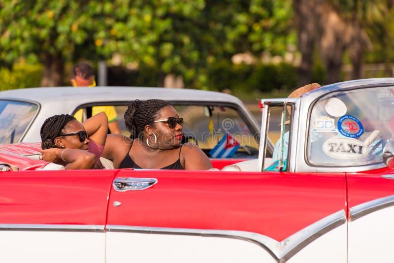 KUBA HAVANNACIGARR - MAJ 5, 2017: Afrikanska kvinnor sitter i en amerikansk retro cabriolet Närbild royaltyfria foton