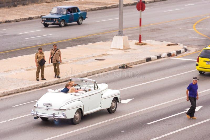KUBA HAVANNACIGARR - MAJ 5, 2017: Amerikansk vit retro cabriolet på stadsgatan Kopiera utrymme för text royaltyfria bilder