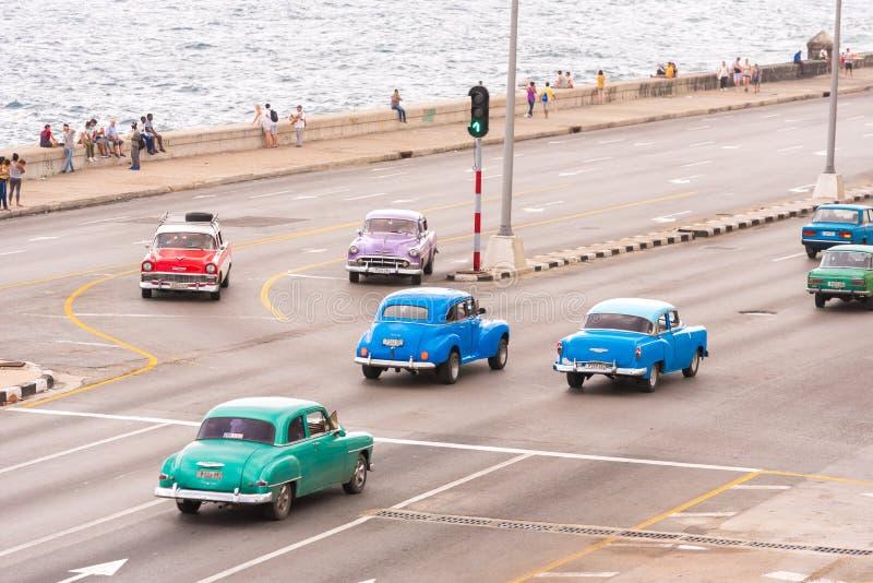 KUBA HAVANNACIGARR - MAJ 5, 2017: Cmerican kör retro bilar längs den Malecon stranden Kopiera utrymme för text royaltyfria bilder