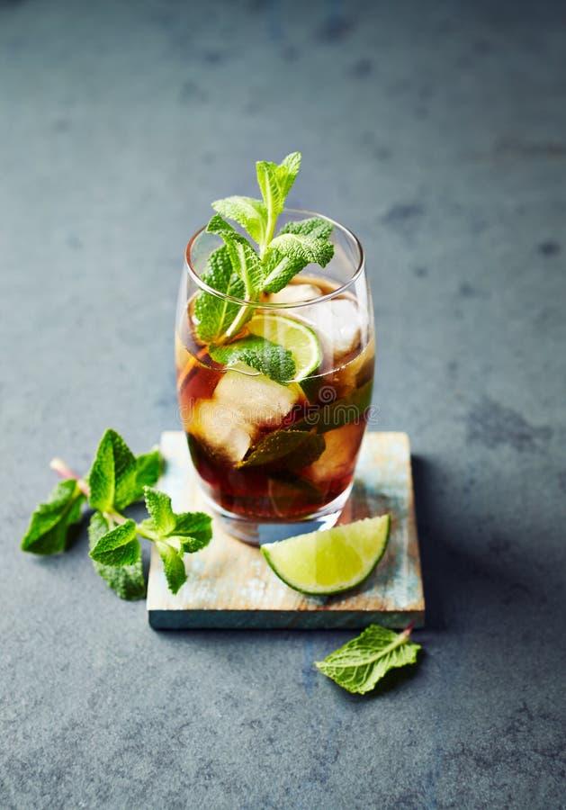 Kuba Libre i en exponeringsglasrom med cola, limefrukt, mintkaramellsidor och is royaltyfri foto