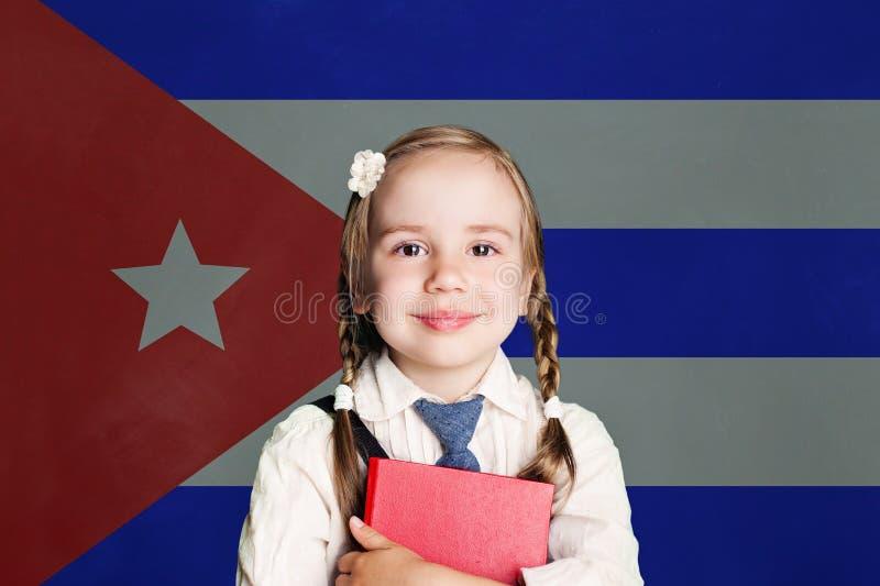 Kuba pojęcie z szczęśliwym dziecko dziewczyny uczniem z książką przeciw fladze Kubański tło obrazy royalty free