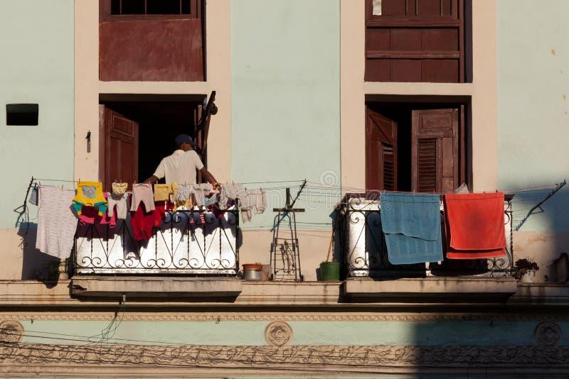 Kubaner auf dem Balkon eines alten Spanisch-ähnlichen Hauses auf Hintergrund des alten Balkons stockfotografie
