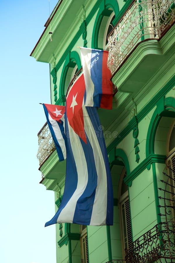 Kubaner fahnenschwenkend gegen ein Gebäude lizenzfreie stockfotografie