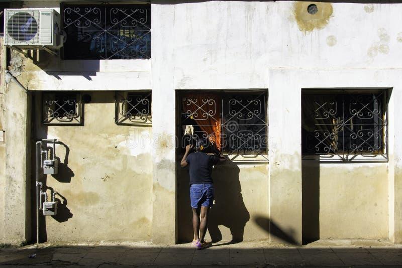 Kubanische Frau untersucht ein Straßenfenster lizenzfreies stockbild