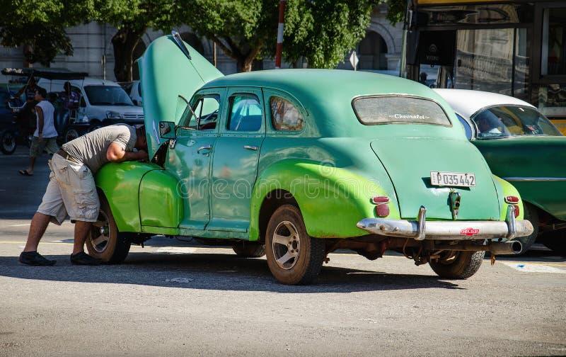 Kubanischer Mann, der gebrochenes klassisches amerikanisches Auto auf Straßen von Havana repariert lizenzfreies stockbild