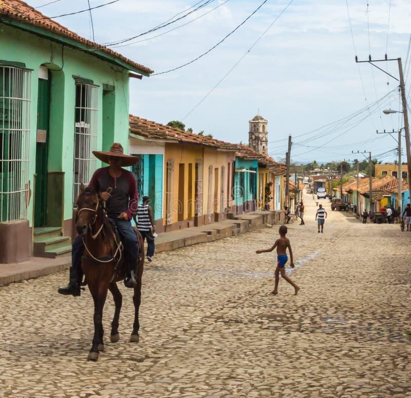 Kubansk cowboy som rider en häst på den bärande sombreron för kullerstengata i Trinidad, Kuba arkivbild