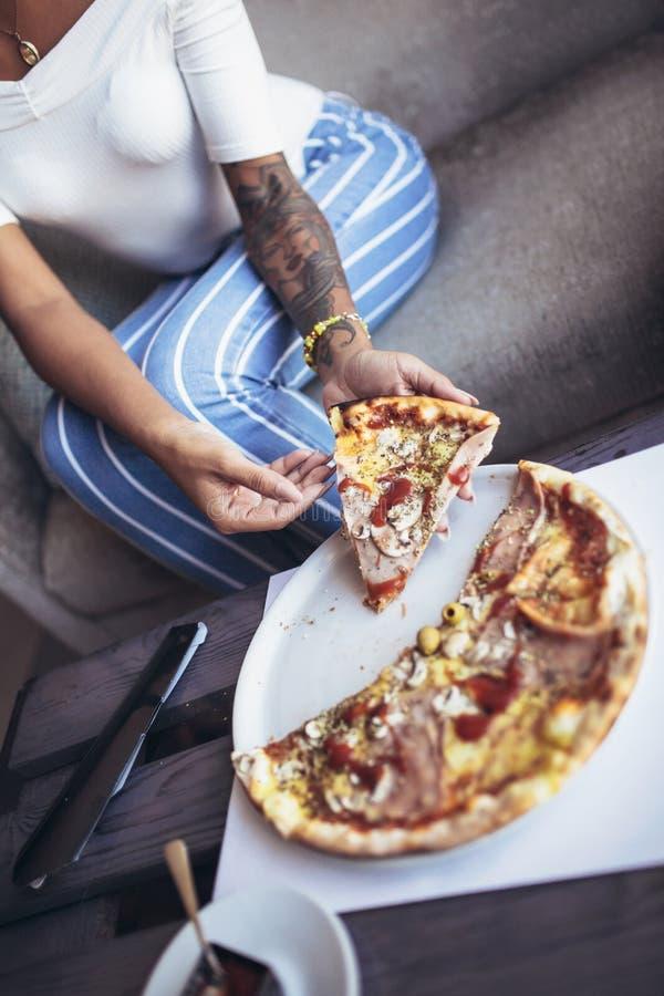 Kubansk kvinna för barntatuering som äter pizza i kafé royaltyfria bilder