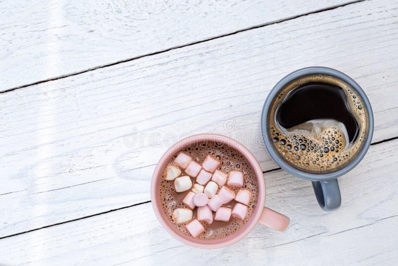 Kubek gorąca czekolada z małymi marshmallows obok kubka odizolowywającego na bielu czarna kawa malował drewno z góry Przestrze? d zdjęcia stock