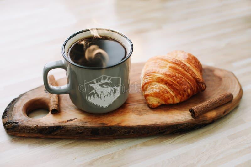 Kubek gorąca kawa i croissant na drewnianej tacy śniadaniowy kawowy pojęcia filiżanki jajko smażący obraz stock