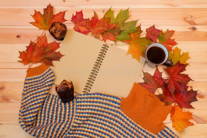 Kubek gorąca kawa, pusty notatnik, jesień liście klonowi, słodka bułeczka i grże domowej roboty pulower fotografia royalty free