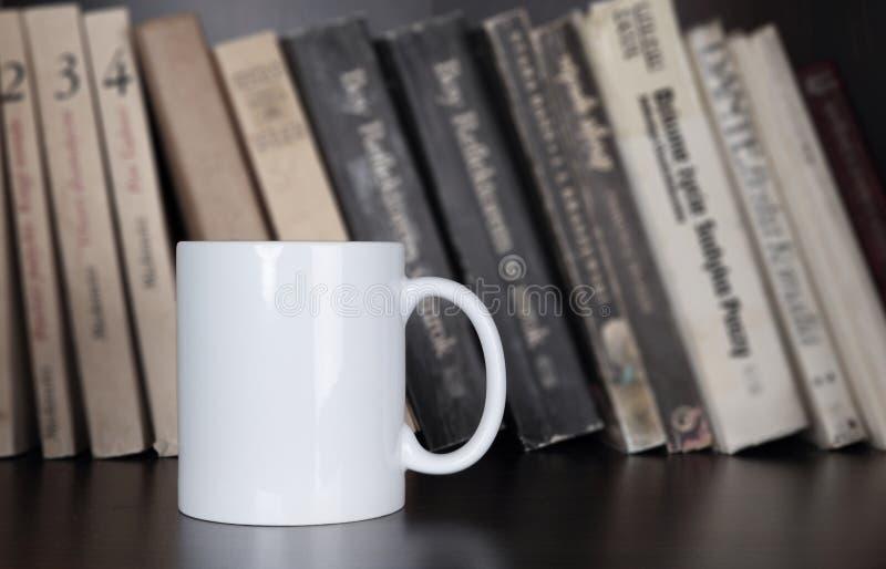 Kubek na półka na książki zdjęcia stock