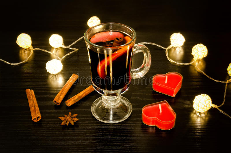 Kubek rozmyślający wino z pikantność, świeczki w formie serca, cynamonowi kije, gwiazdowy anyż Iluminacja rattan lampiony na a zdjęcie stock