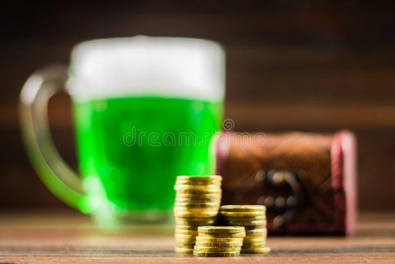 Kubek zielony piwo na stole koniczyna liść Klatka piersiowa złoto, moneta stos StPatrick 's dzień zdjęcie royalty free