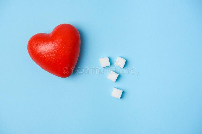 Kuber av socker och röd hjärta på en blå bakgrund royaltyfri bild
