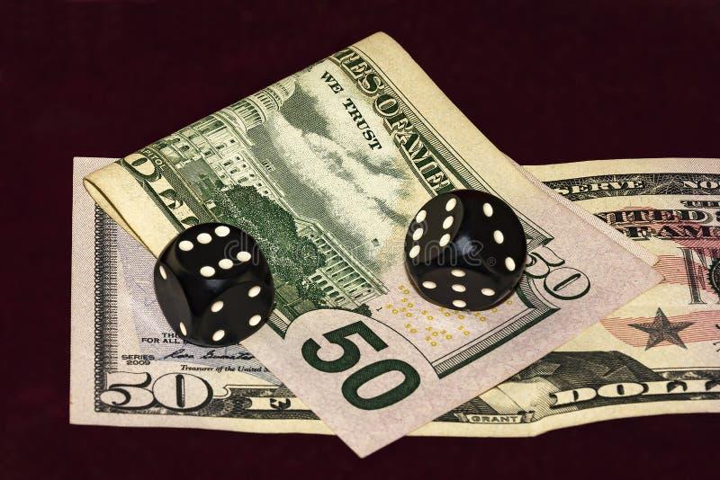 Kuber för poker och delen av femtio dollar sedlar ligger på CR royaltyfri bild
