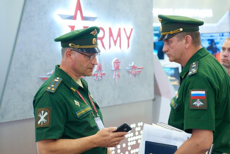KUBINKA, RÚSSIA, AGOSTO 24, 2018: Dois oficiais de exército do russo no uniforme verde que falam entre si na técnica militar inte foto de stock royalty free