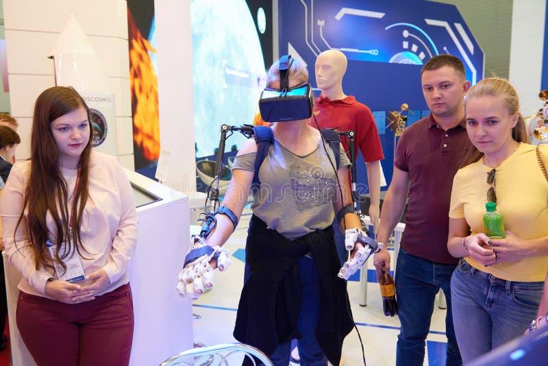 KUBINKA, RUSLAND, AUGUSTUS 24, 2018: Het jonge meisje in exosuit en virtuele werkelijkheidsglazen probeert om ruimterobot op comp royalty-vrije stock afbeelding