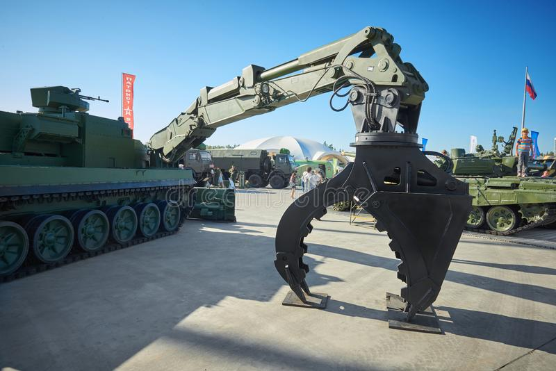KUBINKA, RUSSIA, AUG.24, 2018: Special military excavator with toothed arm for fallen trees removing on tank platform. Russian wea stock images
